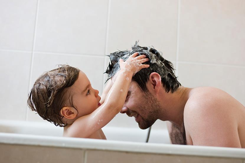 toddler washing fathers hair in the bathtub