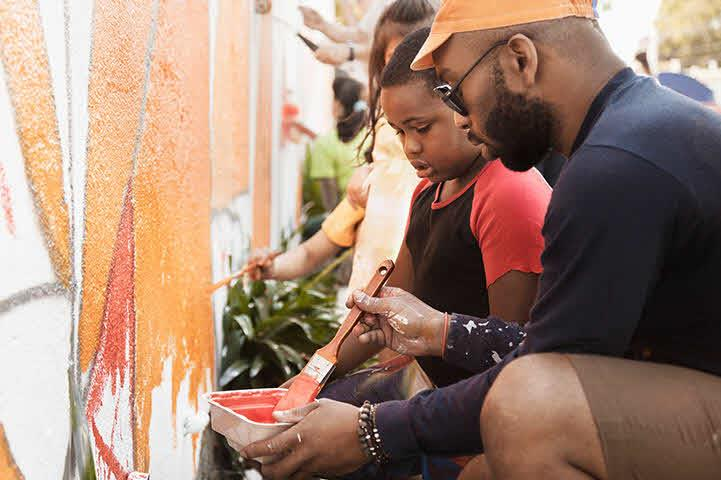 A father and his son are painting a wall together.