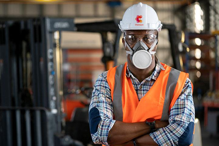 A worker in a facility wearing personal protective gear.