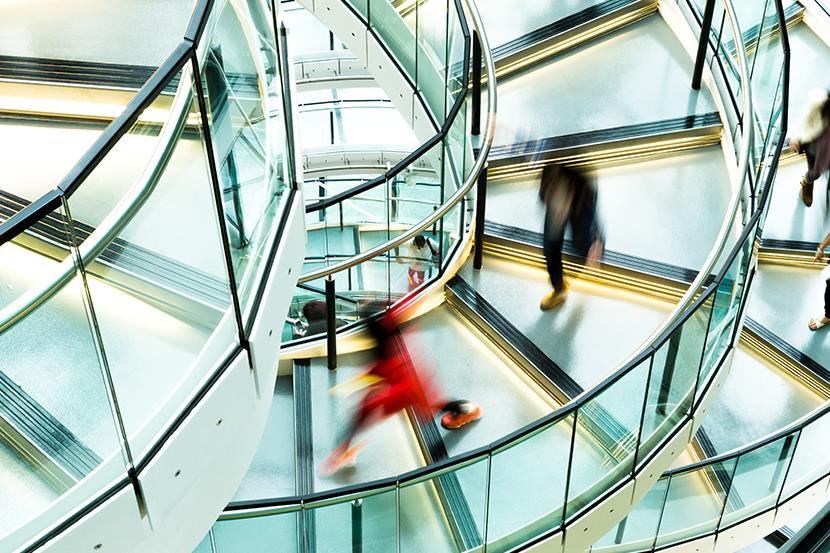 blurred figures walking down a modern steel and glass spiral staircase