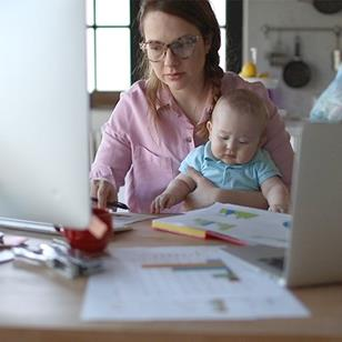 A mother is working at home, on her computer, while holding her baby.