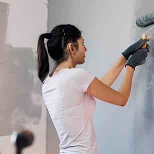 A woman wearing gloves painting wall, at home.