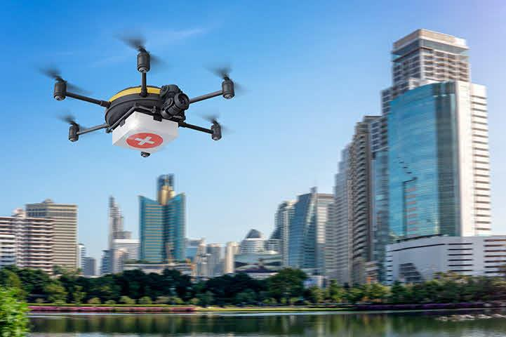 An image of a drone flying over a city lake.