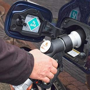 An image of a hand filling a car with hydrogen fuel.