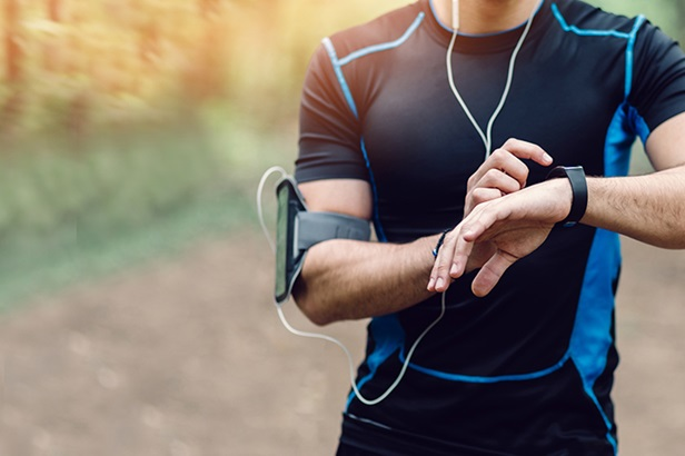 man in black running attire and wearing arm band with smartphone checking watch