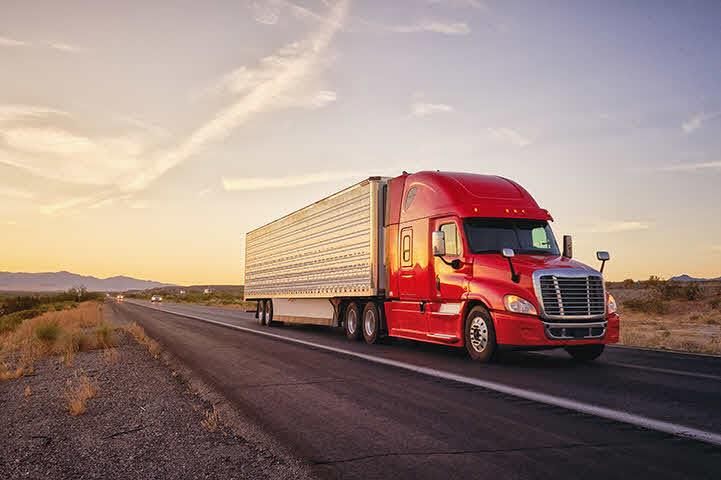 An image of a red tractor trailer driving down the highway near sunset.