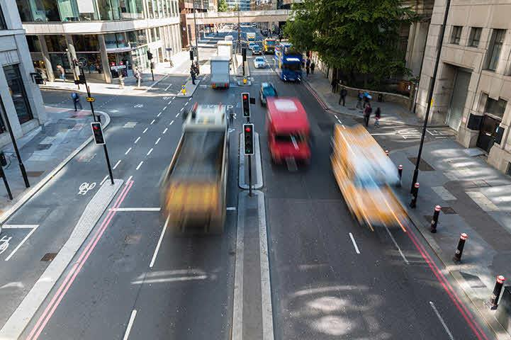 An image of vehicles traveling down a one way highway within the city.