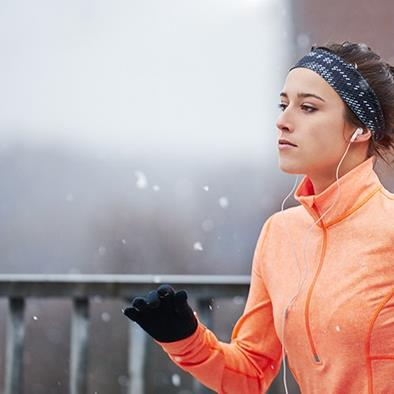 woman in orange jacket and black gloves running outside in snow