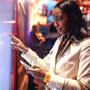 An image of a woman standing in front of a touchscreen holding a phone.