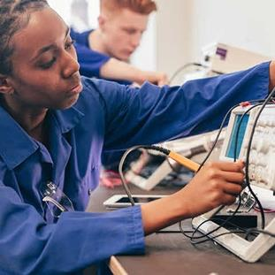 A young women studying STEM experimenting with electronics.