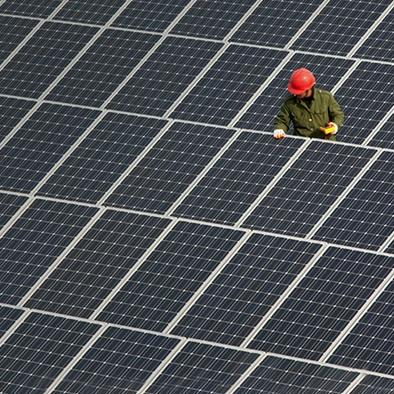 worker in red hardhat checking out solar panels