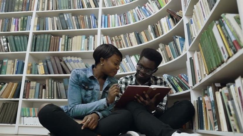 Two Black students studying in a library together.