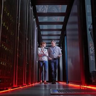 man and woman walking and talking together in a server room that has red floor lights