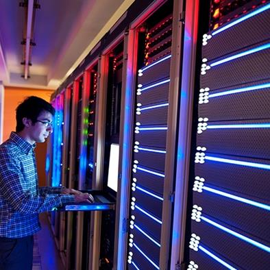 man typing on keyboard in datacenter room with wall of servers