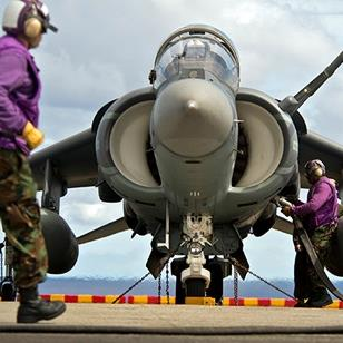 one man in bdu walking in front of a harrier jet while another man adds fuel