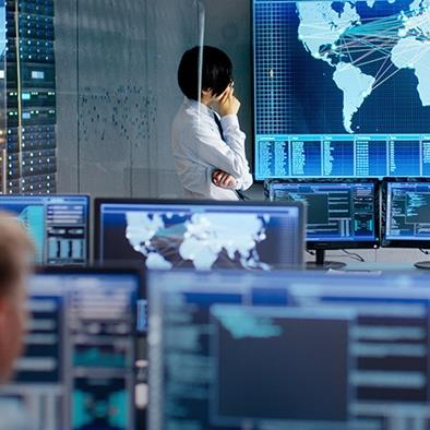 person in control room standing in front of large screen that is projecting a world map