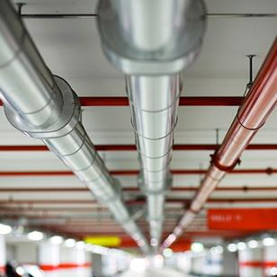 pipes running the length of a parking garage ceiling