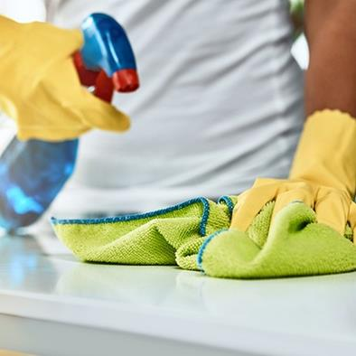 person wearing yellow gloves spritzing cleaning bottle and wiping counter clean with green cloth