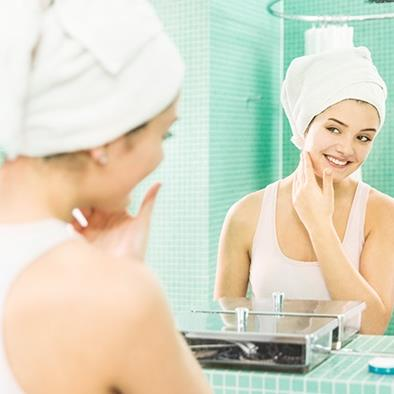 woman looking at self in mirror while applying lotion