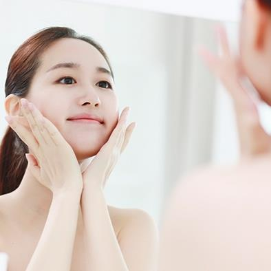 woman looking in mirror holding her face in her hands