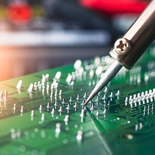person soldering a green computer circuit board
